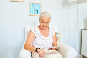 Senior woman sitting in sofa and using smart watch and digital tablet