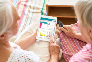 Image of two senior women looking at a dashboard on a tablet