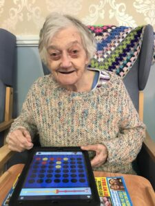 Resident of Wicksteed holds an iPad playing a game