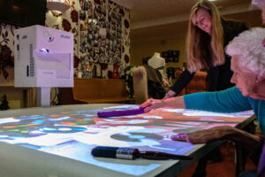Image shows projector on wheels reflecting onto a table where older people use it to play a game