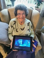 An image of a smiling woman holding an iPad. The iPad has an image from 'A Christmas Carol' from the live streaming of the Old Vic Theatre performance in December 2020